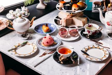 Zestaw angielskiej popołudniowej herbaty zawierający gorącą herbatę, ciasto, bułeczki, kanapki i mini placki na marmurowym blacie.