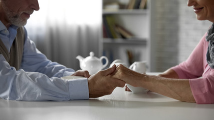 Senior male holding his wifes hand, sitting at table with cup of tea, happiness
