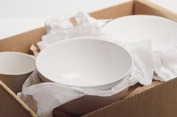 Clean white dishes in paper packed in a cardboard box. Concept relocation