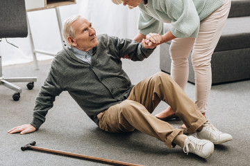 old woman helping to stand up husband who falled down on floor near walking stick