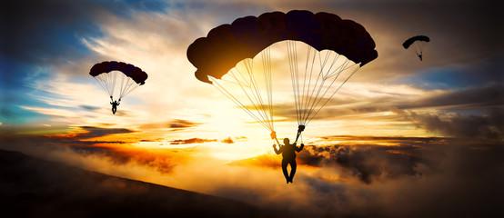 Sylwetka spadochroniarza lądowania o zachodzie słońca
