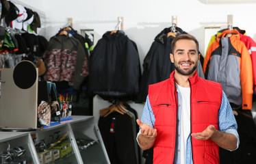 Sprzedawca stojący w pobliżu wieszaków z odzieżą wędkarską w sklepie sportowym. Miejsce na tekst