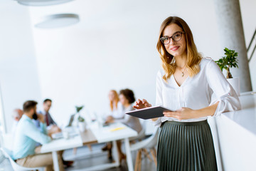 Elegant businesswoman standing in office with digital tablet