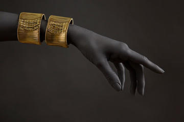 Black woman's hand with gold jewelry. Oriental Bracelets on a hand. Gold Jewelry and luxury