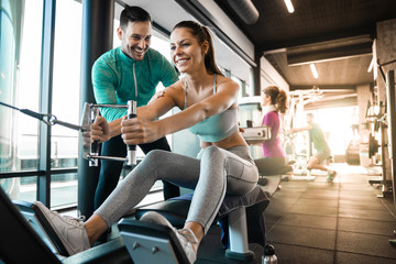 Happy athlete doing rowing workout with personal trainer in the gym