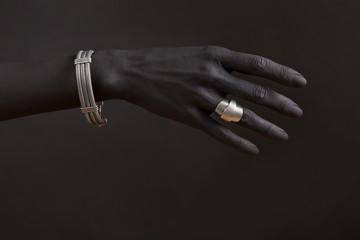 Black woman's hand with Silver jewelry.