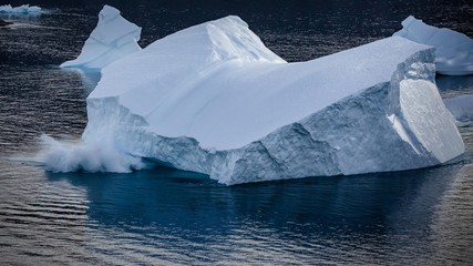 large crashing iceberg  in  the  fjords of East Greenland in summer