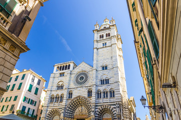 Facade of San Lorenzo Cathedral catholic church on Piazza San Lorenzo square among buildings in historical centre of old european city Genoa Genova with blue sky background, Liguria, Italy