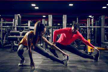 Strong fit beautiful couple is stretching muscles after a hard training in a gym.