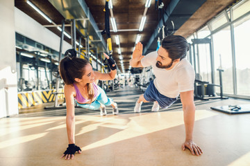 Sporty couple doing push-ups and giving high five. Gym interior.