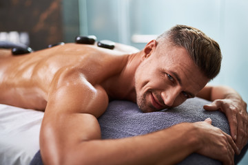 Handsome young man lying on massage table while having spa treatment