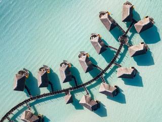 Luksusowe wille nad wodą z palmami kokosowymi, błękitną laguną, białą piaszczystą plażą na wyspie Bora Bora, Tahiti, Polinezja Francuska