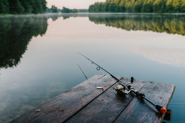 Fishing rod, spoon, hooks on a brown wooden background. fishing bait. close up. throw-line. fishing rod. Rod on the bridge. Bridge passes through the lake, river. flat lay. top view.