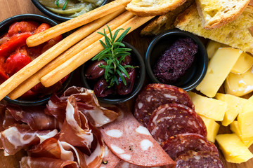 Delicious anti-pesto platter provided by gourmet Italian cuisine restaurant featuring a variety of meats, cheeses, olives and dips.
