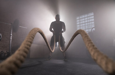Silhouette of man working out with battle ropes at gym.