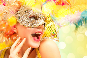 Beautiful surprised woman in carnival mask. Beauty model woman wearing masquerade mask at party over holiday background with magic glow. Christmas and New Year celebration. Glamour lady with perfect
