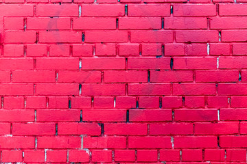 the brick wall is painted in pink color