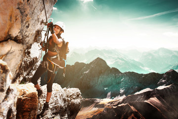 Girl climbing on a Via Ferrata