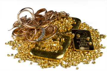 A pile of gold bars, gold jewelry and gold granules. Isolated on white background. Selective focus.