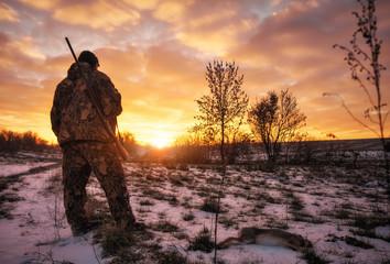 Zimowe polowanie na zające o wschodzie słońca. Hunter porusza się ze strzelbą i szuka ofiary.