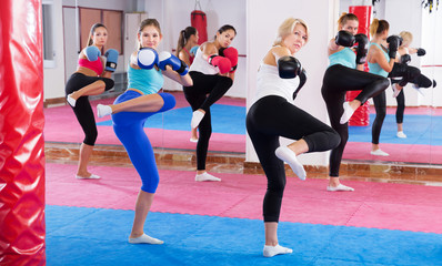 women are boxing and doing kick with coach