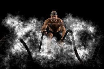 Men working out with battle ropes. Dark smoke background