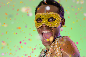 Carnaval Brazil. Excited and Cheerful. Throwing confetti. Portrait of black man dressed up for the holiday. Bright background. Party concept, celebration and festival.