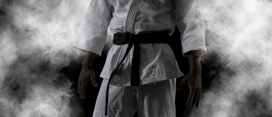 Facet pozuje w białym kimonie z czarnym pasem. Retusz czarny