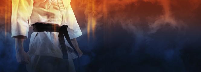 Facet pozuje w białym kimonie z czarnym pasem.
