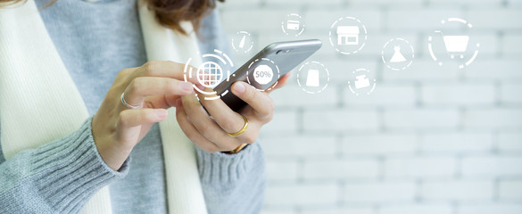 close up woman hand holding smartphone with virtual interface of shopping online circle technology concept.