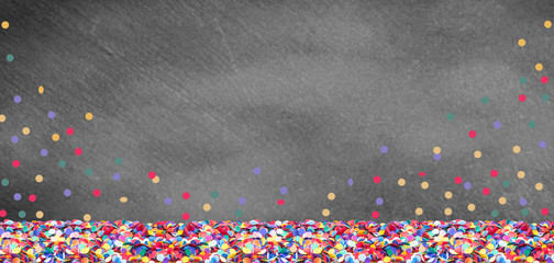 Colorful confetti in front of a slate board for carnival