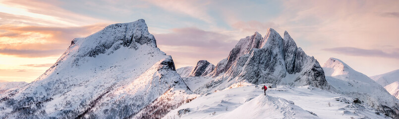 Panorama of Steep peak mountains with covered snow and mountaineer man backpacker