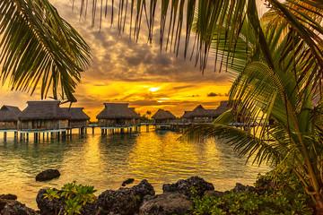 Wybrzeże z tropikalną plażą i turkusową wodą wewnętrznej laguny atolu Tikehau o zachodzie słońca. Archipelag Tuamotus, Polinezja Francuska, Ocean Południowy Pacyfik.