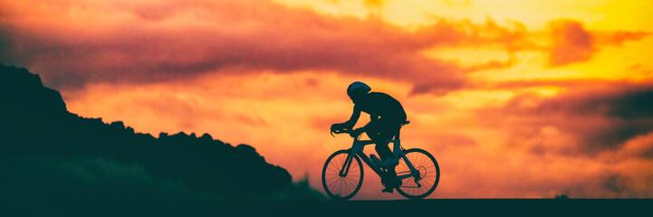 Road bike triathlon race cyclist on racing bike biking competition at sunset background sky banner panorama.