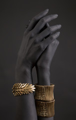 Black woman's hand with gold jewelry. Oriental Bracelets on a black painted hand.