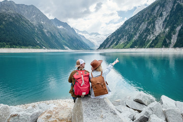 Travelers couple look at the mountain lake. Travel and active life concept with team. Adventure and travel in the mountains region in the Austria. Travel - image