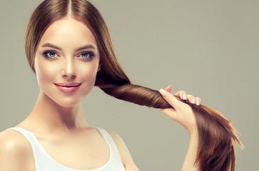 Piękna modelka z błyszczącymi brązowymi i prostymi długimi włosami. Prostowanie keratyny. Zabiegi lecznicze, pielęgnacyjne i spa. Gładka fryzura