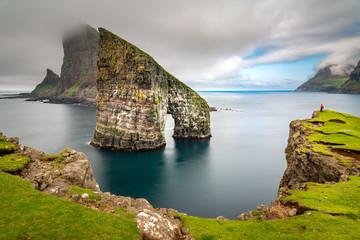 Drangarnir rocks at Faroe Islands, Europe. Hiker admiring the view