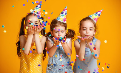 happy birthday children girls with confetti on yellow background