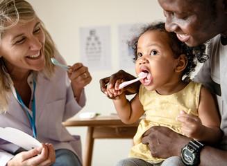 Dentysta uczy małą dziewczynkę, jak myć zęby