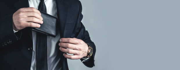 Businessman pulls his leather wallet into suit pocket.