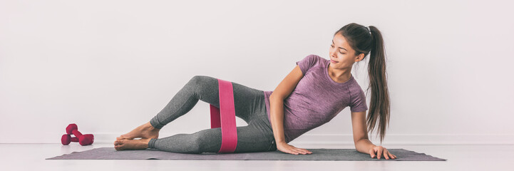 Resistance band clamshell exercise fit girl training legs on floor mat demonstration. Hip abductor workout for burning calories. Banner panorama.