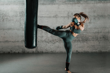 Caucasian woman in sportswear and with boxing gloves kicking bag in the gym. Full length. Wall in background.