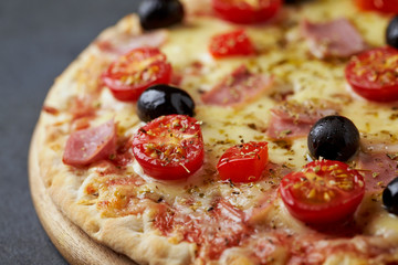 Pizza with ham, mozzarella cheese, cherry tomatoes, red pepper, black olives and oregano. Home made food. Concept for a tasty and hearty meal. Black stone background. Copy space