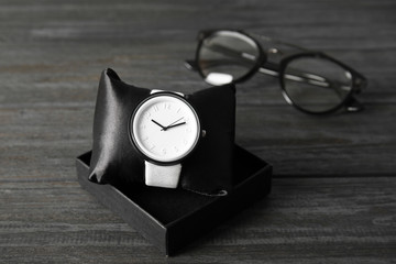 Composition with stylish wrist watch on wooden background. Fashion accessory