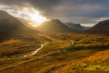 Winding Road And River Leading Through The Glencoe Valley With Golden Evening Light.