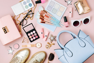 Flat lay of female fashion accessories, makeup products and handbag on pastel color background. Beauty and fashion concept