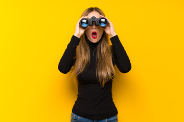 Young pretty woman over yellow background and looking in the distance with binoculars