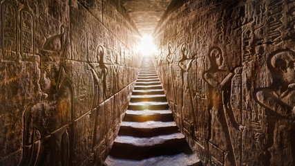 ABYDOS EGYPT Sethi I temple, completed by Ramses II (-1200). Passage flanked by two glowing walls full of Egyptian hieroglyphs, illuminated by a warm orange backlight from a door at the