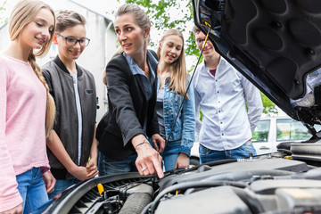 Driving teacher showing class the engine of car
